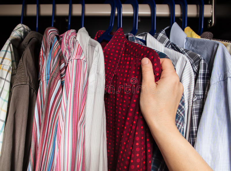 Person chooses shirt in the closet royalty free stock images