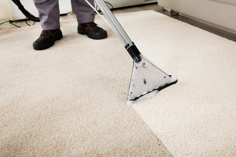 Person Cleaning Carpet With Vacuum-Reiniger lizenzfreie stockfotografie
