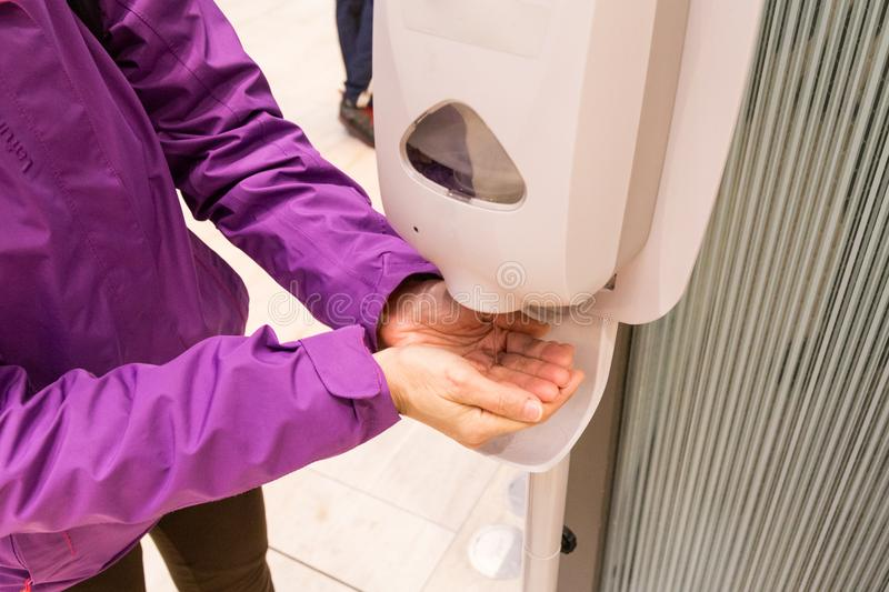 Person cleaning hand with anti-bacterial diinfectant sanitizer i stock image