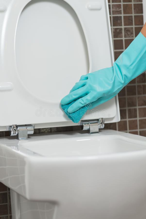 Person Cleaning Under The Rim Of A Toilet Bowl Stock Image