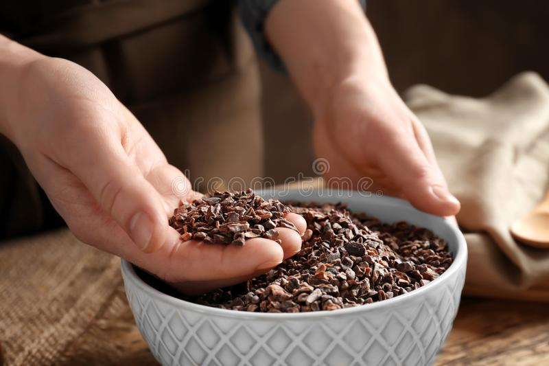 Person with cocoa nibs in hand over bowl royalty free stock photos