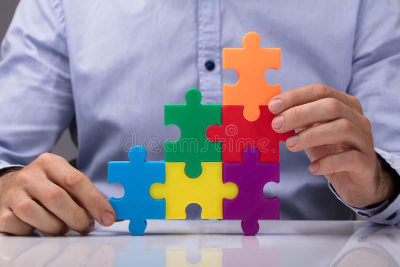 Person Connecting Multicolored Jigsaw Puzzle fotografia stock
