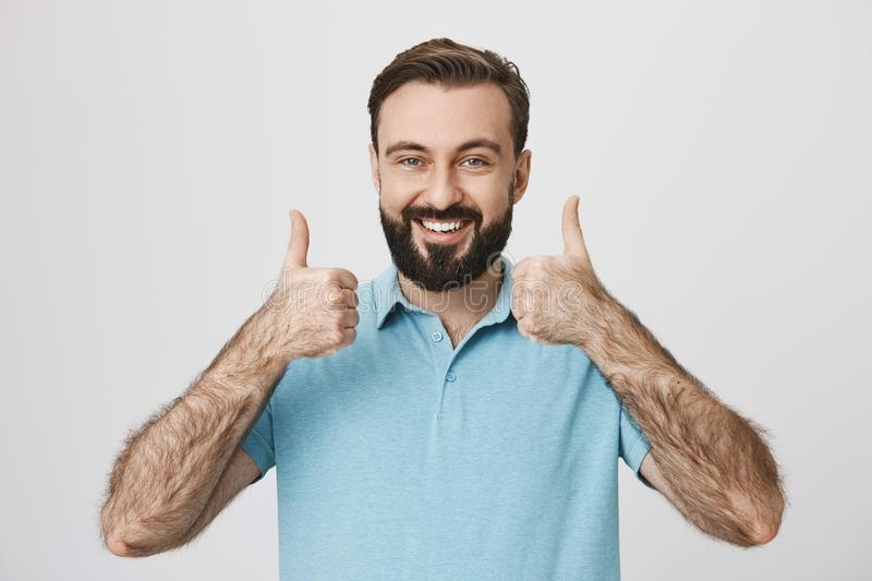 Person with cute beard and moustache thumbs up to show his positive answer standing near white wall. Mature male wearing stock photography