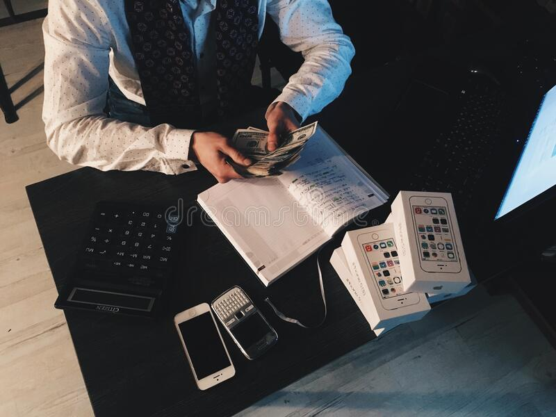 Person Counting Money With Smartphones In Front On Desk Free Public Domain Cc0 Image