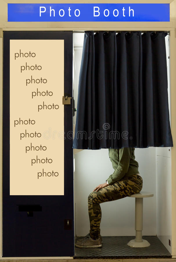 A person covered curtain sits in the photo booth. stock photography