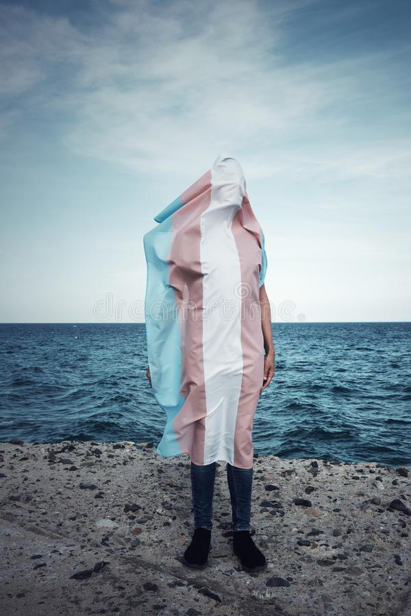 Person covered with a transgender pride flag. A young person covered with a transgender pride flag, with the ocean in the background stock photography