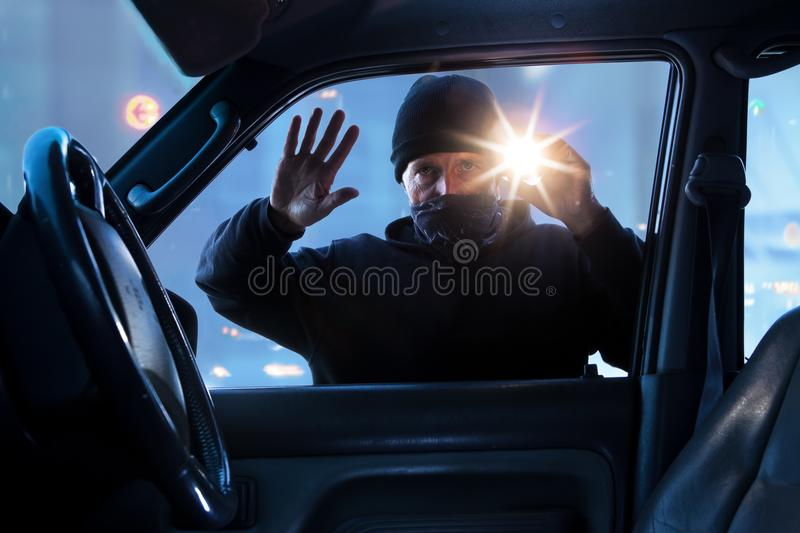 Person,criminal breaking into car at dawn, night. View from inside the car robber criminal breaking in, city background stock photo