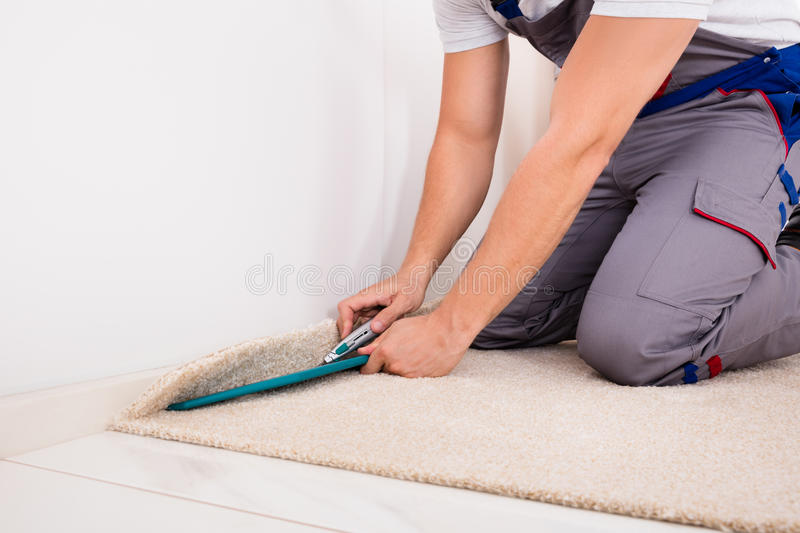 Person Cutting Carpet With Cutter immagine stock