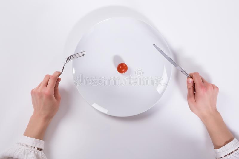 Person Cutting Cherry Tomato On-Plaat royalty-vrije stock afbeelding