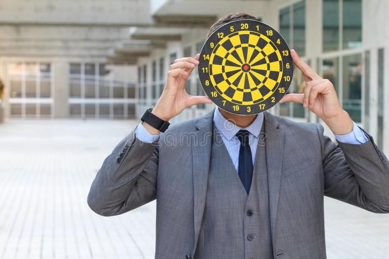 Person with dartboard head in office space stock photo