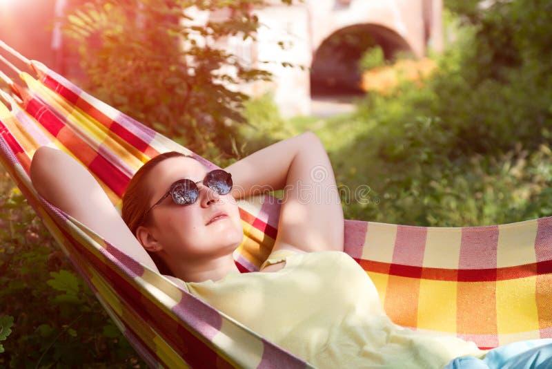 Person in der Sonnenbrille, die im Hügel am Sommer-Garten sich entspannt stockbild