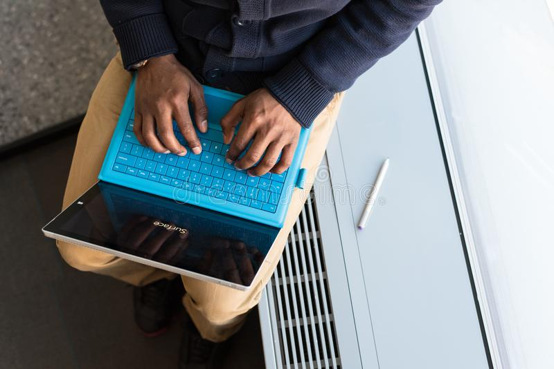 Person, die auf blauem Notebook-Computer tippt stockfotos