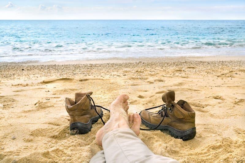 Person, die auf einem tropischen Strand auf dem Sand sich entspannt stockfotografie