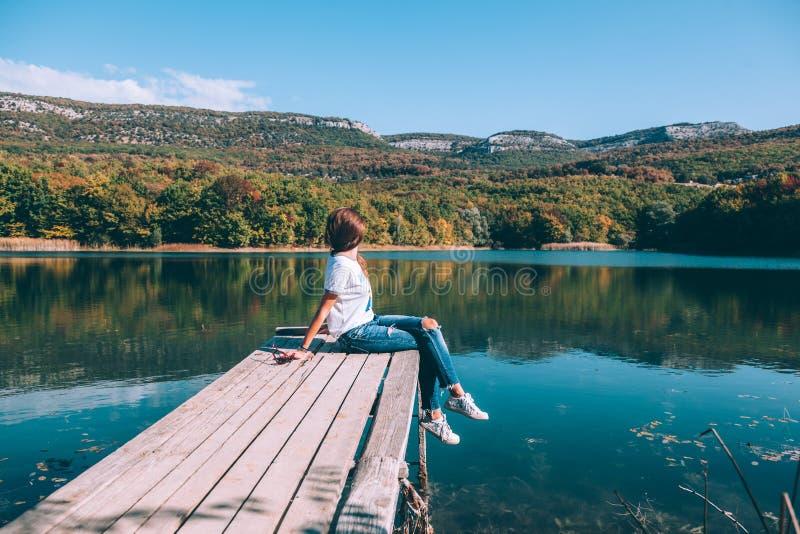 Person, die auf Gleichem durch den See sitzt lizenzfreie stockbilder
