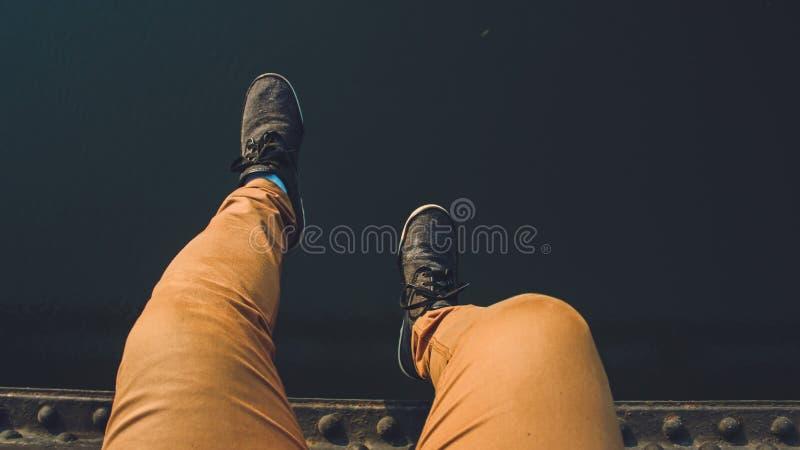 Person, die Brown-Jeans mit Paaren der schwarzen Turnschuhe trägt lizenzfreie stockfotografie