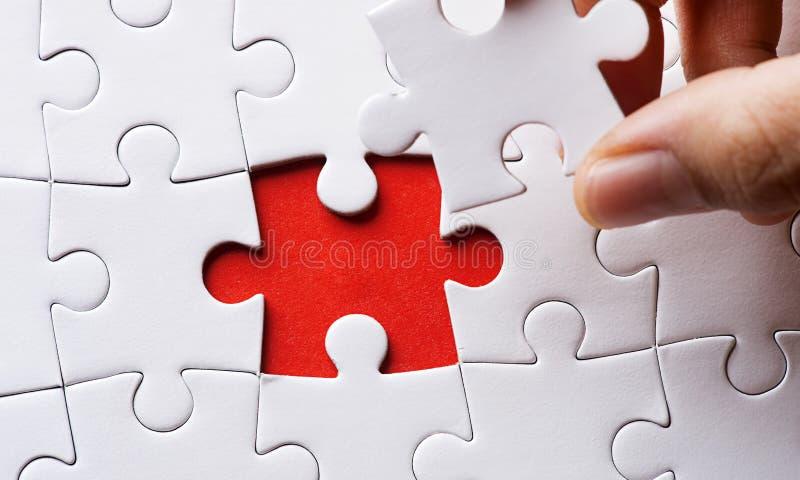 Person, die das letzte Puzzlespielstück passt lizenzfreie stockbilder