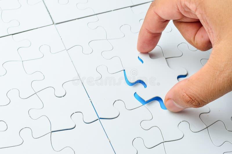 Person, die das letzte Puzzlespielstück passt Geschäftskonzept für den Abschluss des abschließenden Puzzlespielstückes lizenzfreies stockfoto