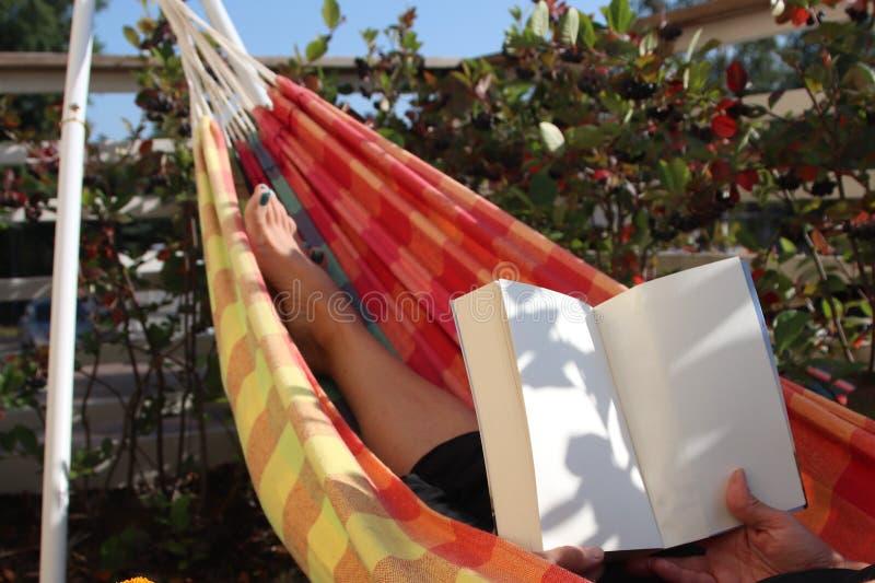 Person, die in der bunten Hängematte sich entspannt lizenzfreie stockfotos