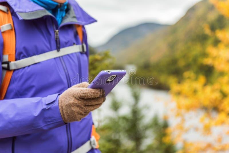Person, die in der Natur unter Verwendung Smartphone App mit Touch Screen Technologiehandschuhen während der Wanderung im Herbstr lizenzfreies stockfoto