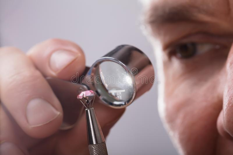 Person, die Diamond Through Magnifying Loupe überprüft lizenzfreie stockbilder