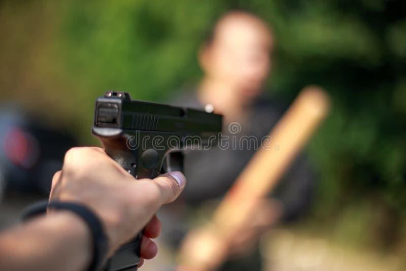 Person, die ein Gewehr auf den Angreifer zeigt Fokus auf Gewehr stockfotos
