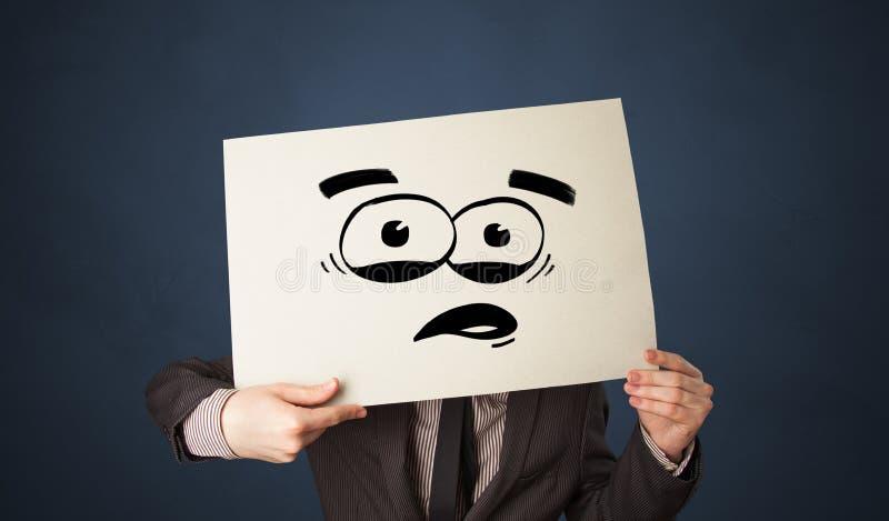 Person, die ein Papier mit lustigem Emoticon vor ihrem Gesicht h?lt vektor abbildung