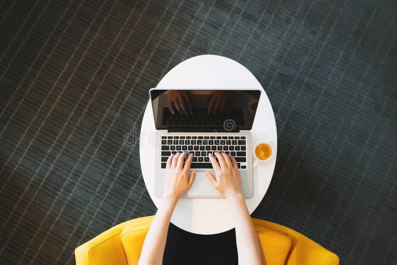 Person, die an einer Laptop-Computer von den Unkosten arbeitet lizenzfreie stockfotos