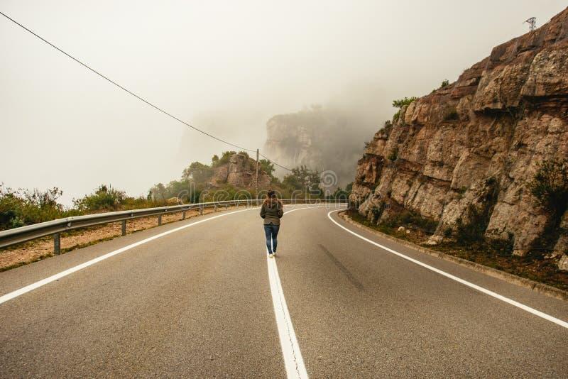 Person, die entlang eine Mittellinie in einer Straße geht lizenzfreie stockbilder