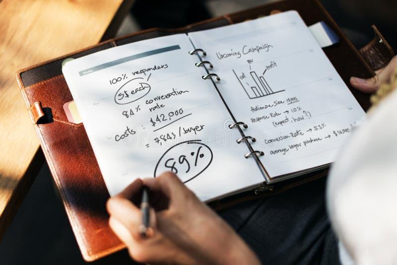 Person, die Finanzberechnungen im Notizbuch macht stockfotografie