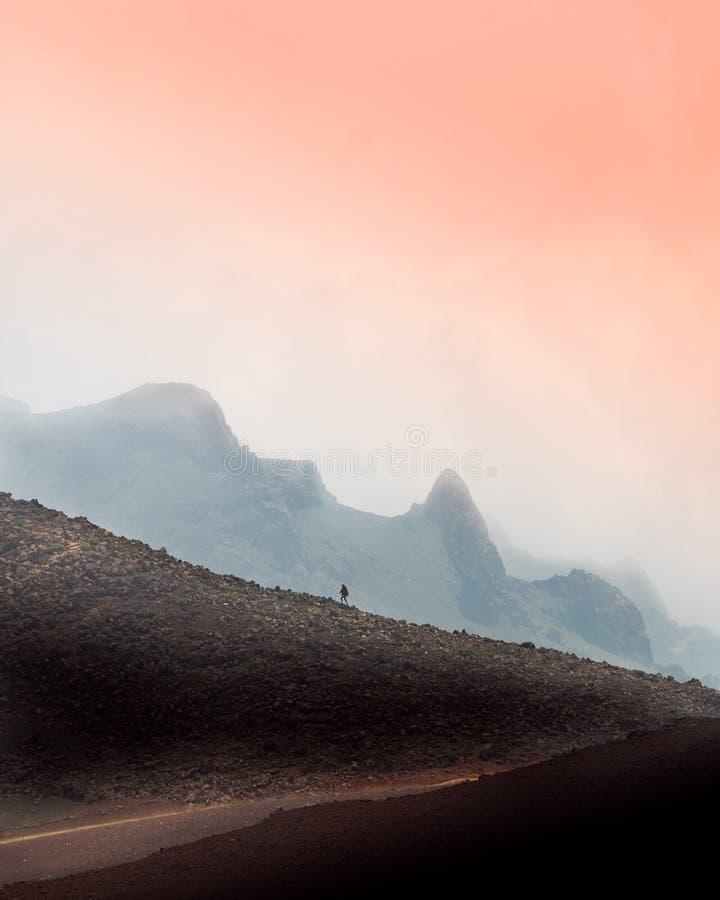 Person, die herauf einen steilen Hang im Abstand mit einem erstaunlichen schönen rosa Himmel im Hintergrund geht lizenzfreies stockbild