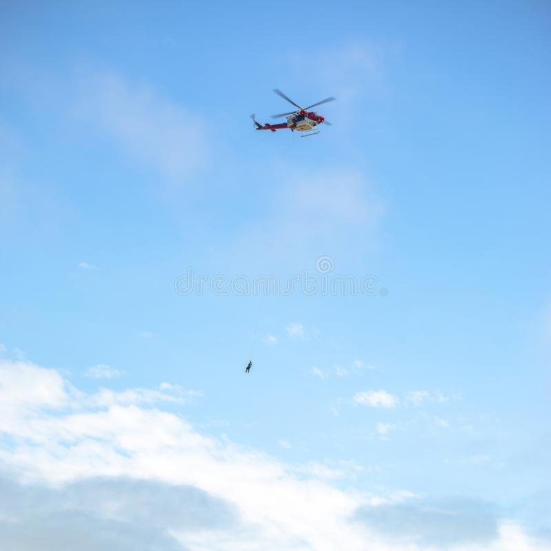 Person, die im Flug durch ein Seil auf einem Hubschrauber haning ist stockbild