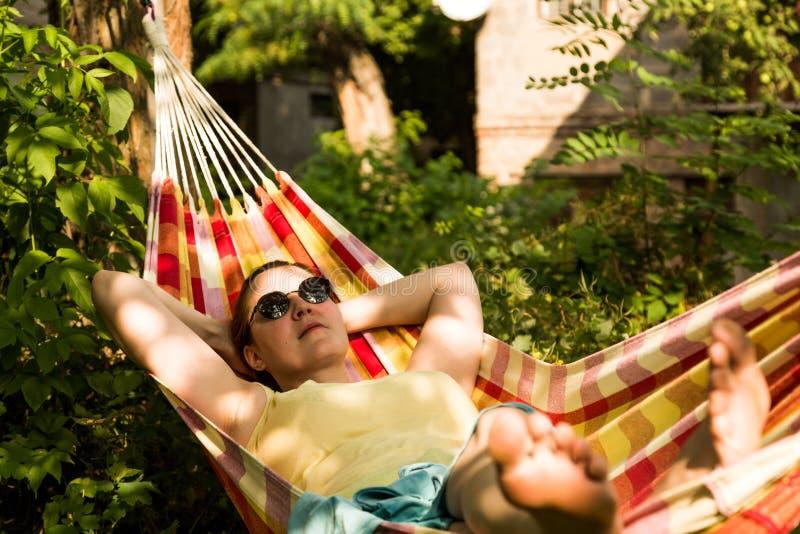 Person, die im Hügel an den hellen Farben des Sommer-Gartens sich entspannt stockfotografie