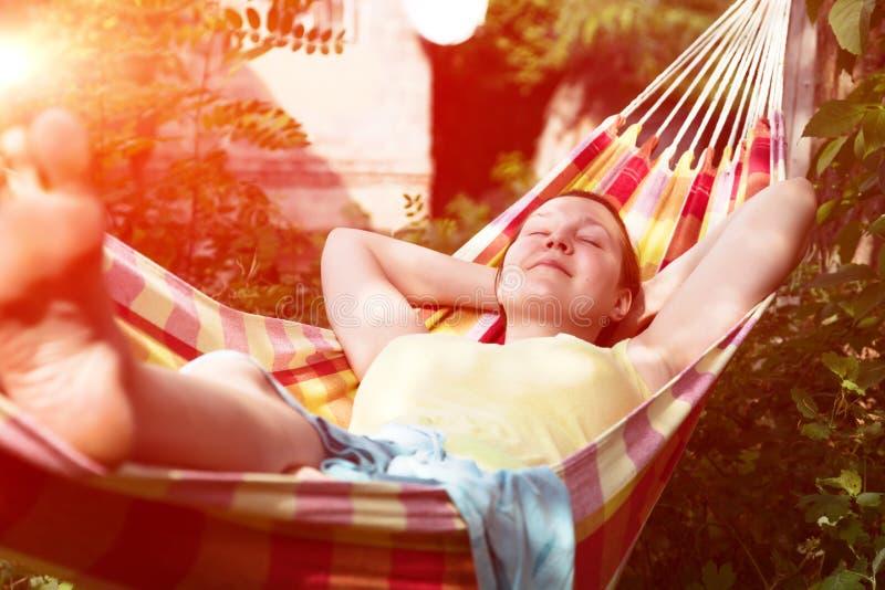 Person, die im Hügel am Sommer-Garten mit Sonnenlicht sich entspannt stockbilder