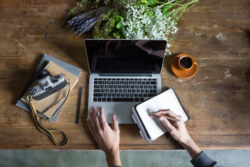 Person, die Laptop und grafische Tablette am Arbeitsplatz mit Notizbüchern und Kamera verwendet lizenzfreie stockfotografie