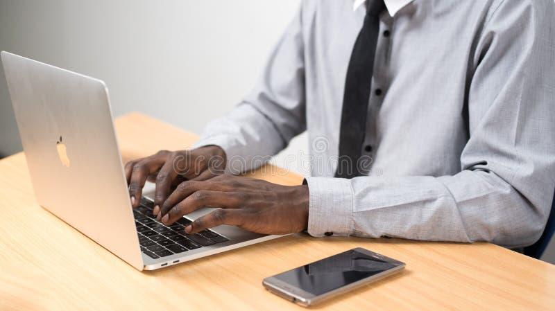 Person, die neben Smartphone neben Laptop vor dem Tisch sitzt lizenzfreie stockfotografie
