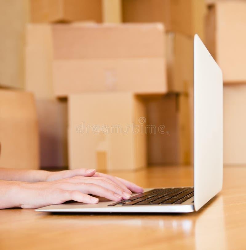 Person, die Notizbuch mit Pappschachteln auf Hintergrund verwendet lizenzfreie stockfotografie