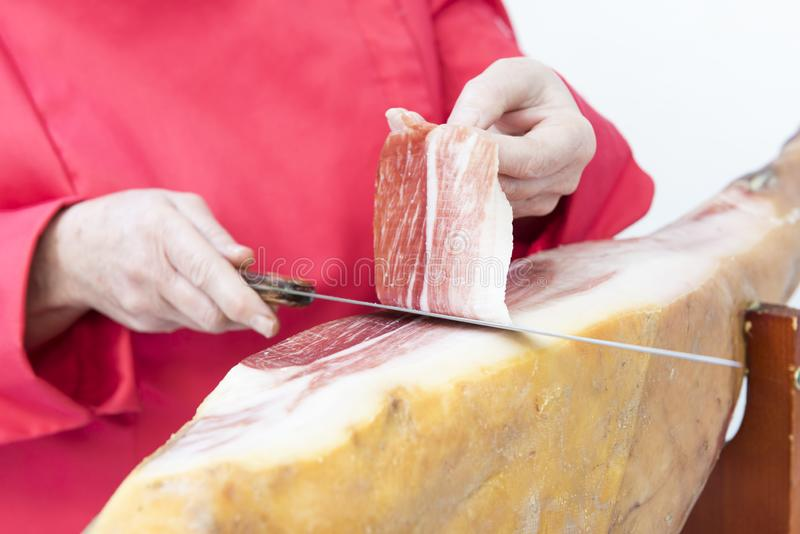 Person, die Schinkenscheiben mit einem Messer schneidet lizenzfreie stockfotografie