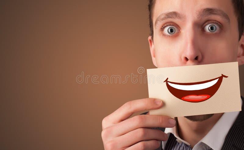 Person, die vor dem Mund eine Karte hält lizenzfreie stockfotografie