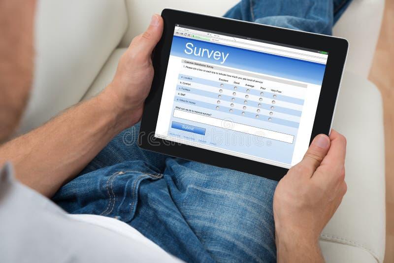 Person With Digital Tablet Showing-Onderzoeksvorm royalty-vrije stock afbeeldingen