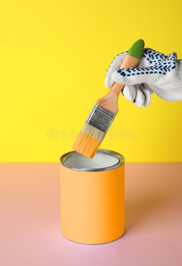 Person dipping brush into can of orange paint on pink table against yellow background, closeup. Mockup for stock image
