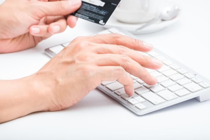 Person entering number of credit card with white workspace. Person do transaction and entering number of credit card with white workspace stock photo
