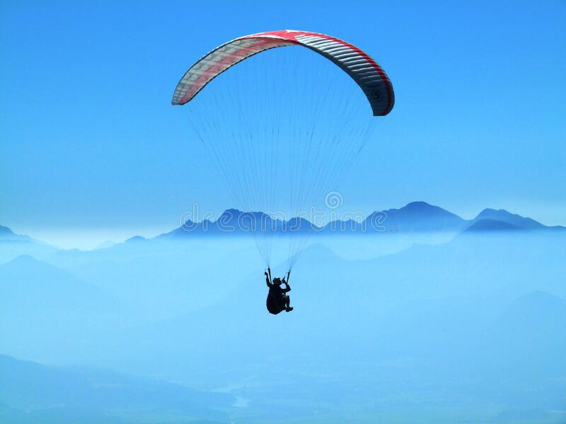 Person Doing Paragliding Above Clouds during Daytime stock image