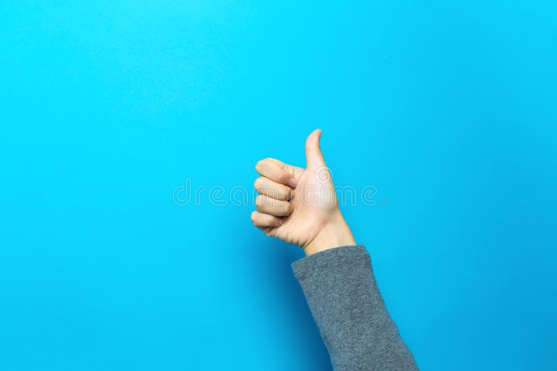 Person doing thumbs up gesture. On a blue background stock photo