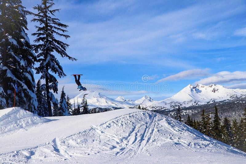 Person Doing Tricks In Mid Air Using Snowboard On Snowfield Mountain royalty free stock photo