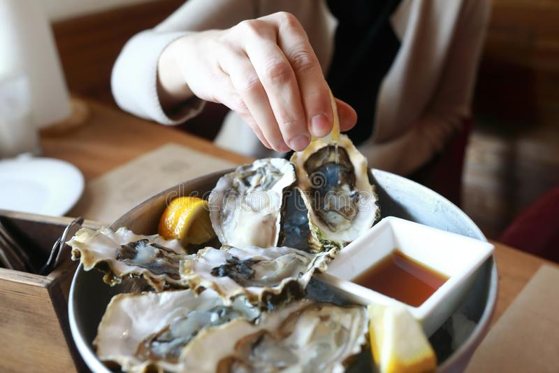 Person dr?ckt Zitronensaft auf Austern zusammen lizenzfreie stockfotografie