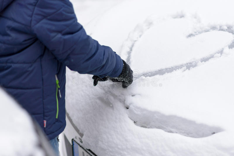 Person drawing a heart in the snow on a car. Person drawing a heart in the snow on the windshield of a snow covered car in winter, symbolic of love and romance royalty free stock image