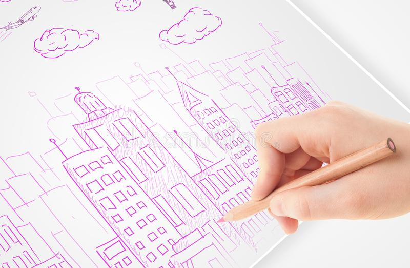 A person drawing sketch of a city with balloons and clouds on a paper. A person drawing sketch of a city with balloons and clouds on a plain papern stock photography