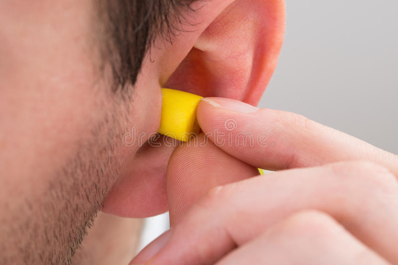 Person Ear With Earplug. Close-up Of Person Ear With Yellow Earplug royalty free stock images