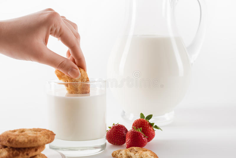 Person eating cookies with fresh milk and strawberries. Close-up partial view of person eating cookies with fresh milk and strawberries stock photo