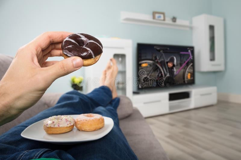 Person Eating Donut While Watching television royaltyfri foto